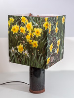 104: Table lamp with ceramic base and photo silk shade with image of daffodils.