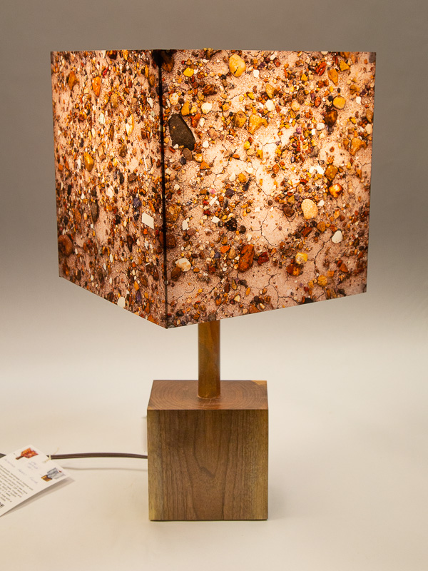 Table lamp with black walnut base and photo silk shade with image of petrified wood pebbles.