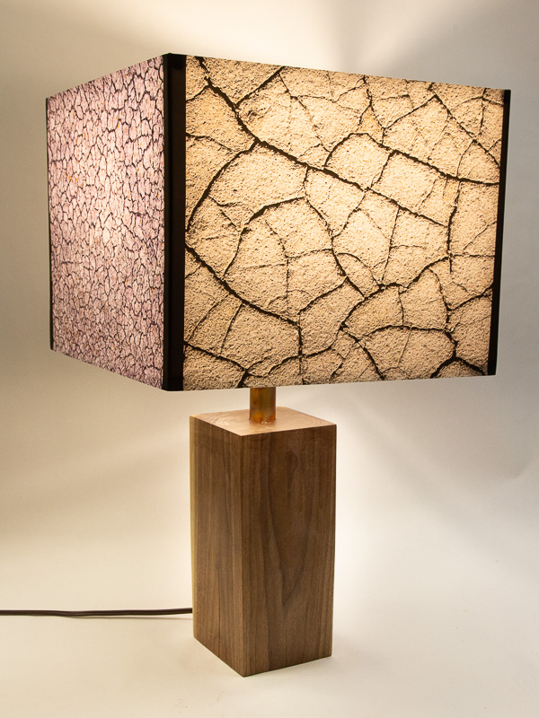 Table lamp with Indiana walnut base and photo silk shade with images of cracked mud and pebbles.