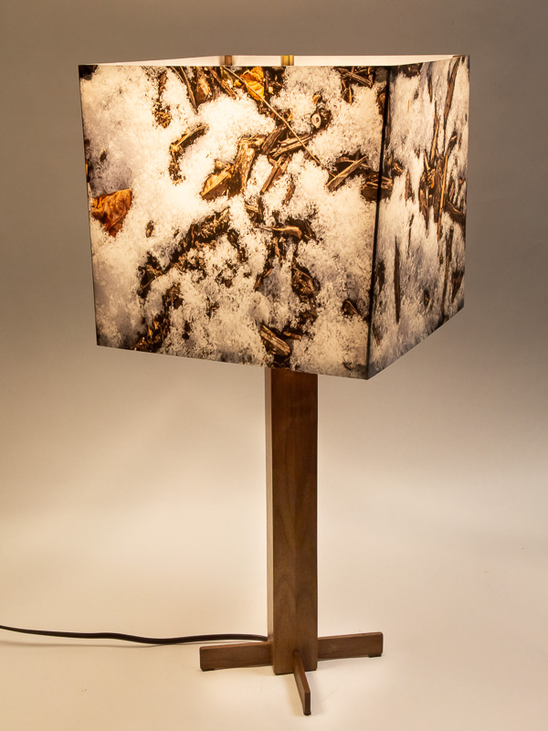 Table lamp with solid black walnut base and photo lampshade with image of melting snow.