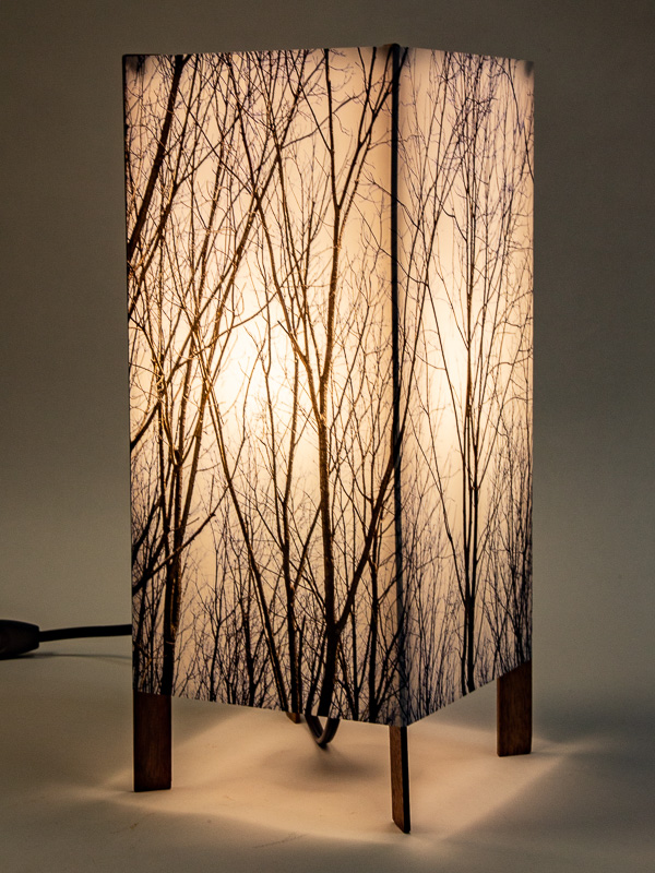 Table lamp with tall basic walnut base and photo silk shade with image of tops of walnut trees.