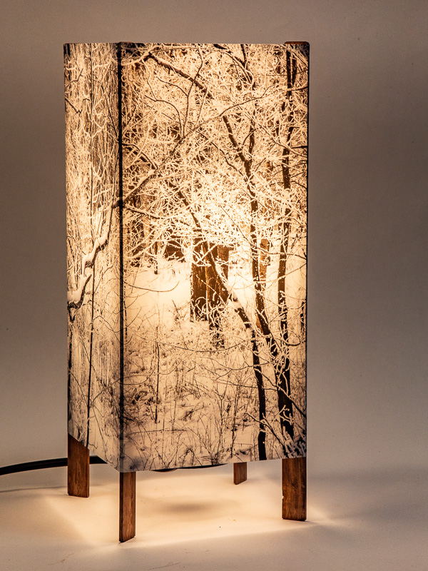Table lamp with tall basic walnut base and photo silk shade with image of hoar frost on trees.